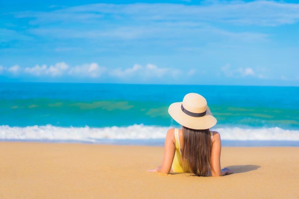 A foto mostra uma mulher deitada exposta ao sol à beira da praia