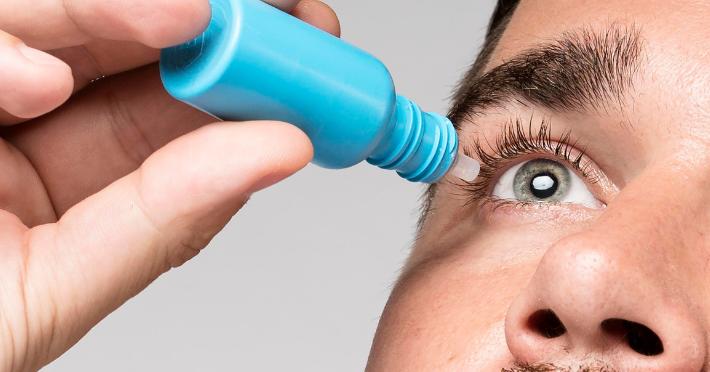 Imagem mostra homem aplicando colírio